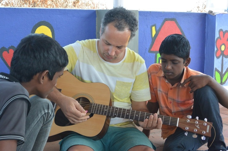 Valéry Lamoure playing guitar with WIDE children